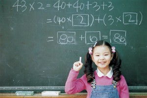 Happy child with a completed math problem on the blackboard